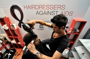 Ricardo Neco, a Mexico City member of Hairdressers Against AIDS, styles the hair of Maria de Socorro Lopez in a booth at the XVII International AIDS Conference in Mexico City.