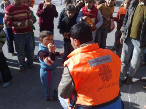 Joumah helps deliver caritas food aid to a Palestinian boy
