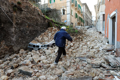 A man walks on debris as he looks for his relatives after an earthquake in L'Aquila