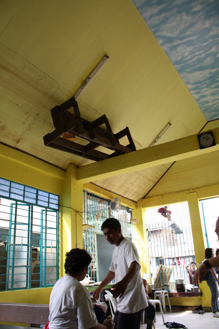 Displaced people receive aid at Our Lady of Perpetual Help Chapel in Rizal, Philippines, following severe flooding. Fr. Javier, in the white T-shirt, broke a hole in his roof when the storm hit and eventually swam from his roof to safety.  A pew is lodged in the rafters of the chapel, where it floated during the flood.