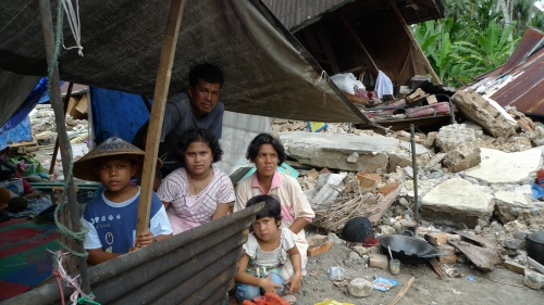 Ilham Zakirman (right) sits with her family in makeshift shelter