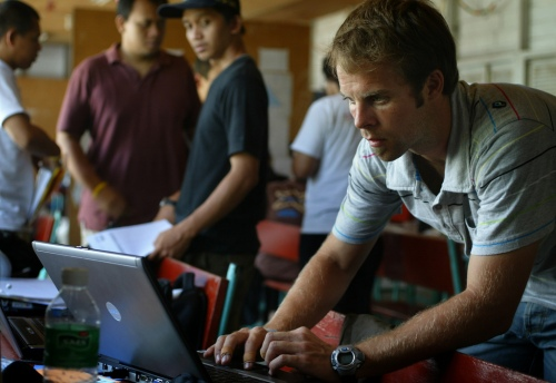 Aid workers under the various umbrellas of Caritas Internationalis including Caritas Germanys' Fabien Tritschler gather for logistics meetings at a makeshift co-ordination centre in Padang, West Sumatra to deliver much needed aid to people who have lost thier homes in the earthquake near Padang City, Indonesia. Photograph by James Alcock/Caritas Internationalis (c) 2009.