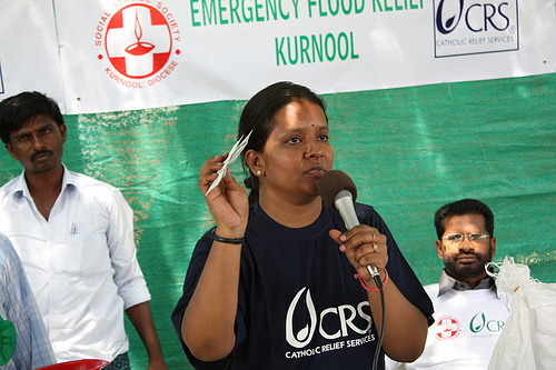 A CRS staffer explains the proper use of water purification tablets to over 1000 villagers whose homes were damaged by flooding in southern India. Credit: CRS