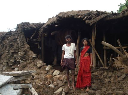 Flood survivors in southeast India stand in front of their destroyed home. Photo by Fr. Jijo Murthanatt for CRS