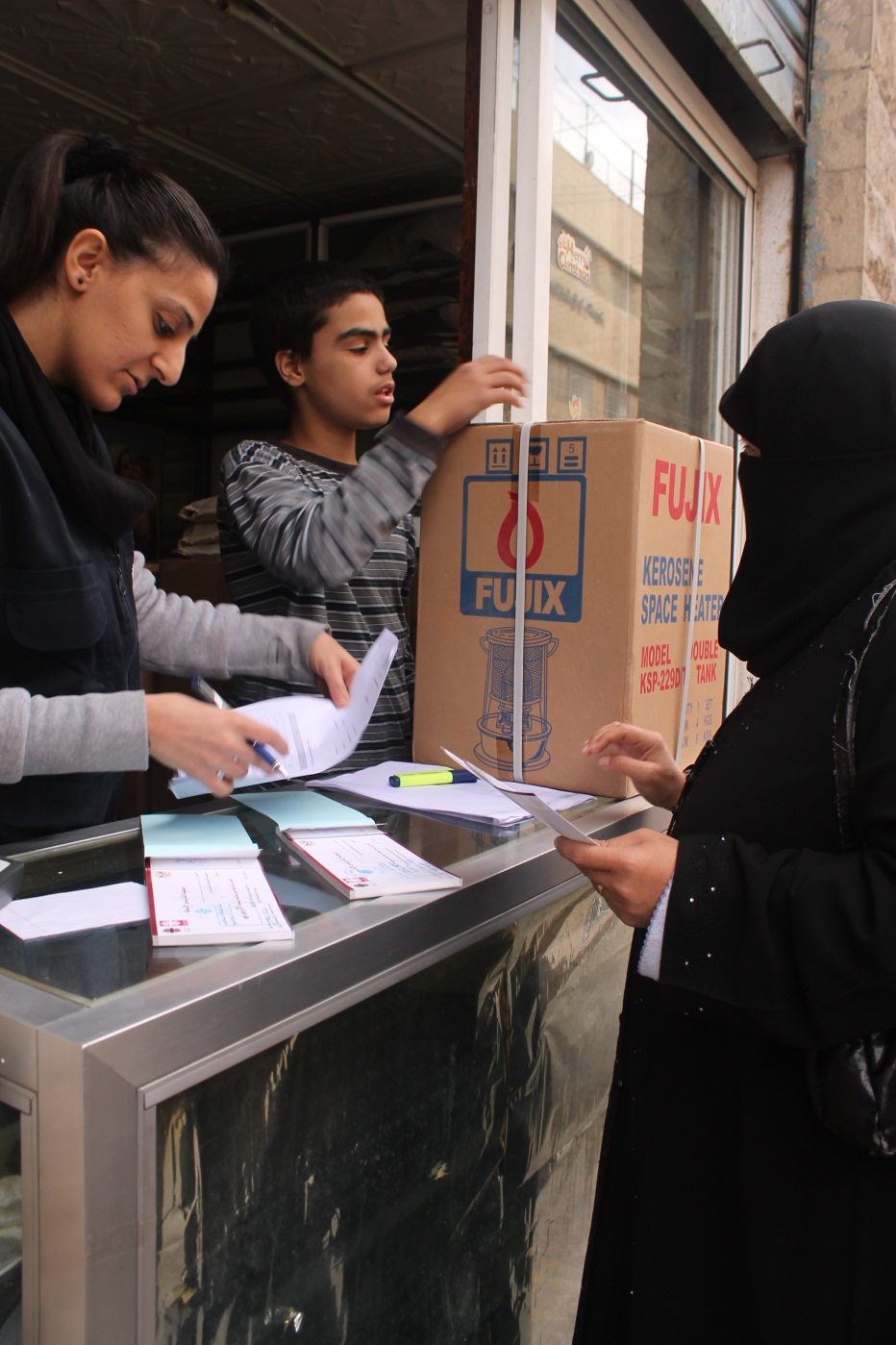 Manal Ahmad, a 30-year old Syrian refugee, using the vouchers she received from Caritas Jordan. Photo by Caritas Jordan