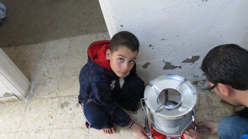 Zarfeh's son puts together a heater supplied by Caritas.