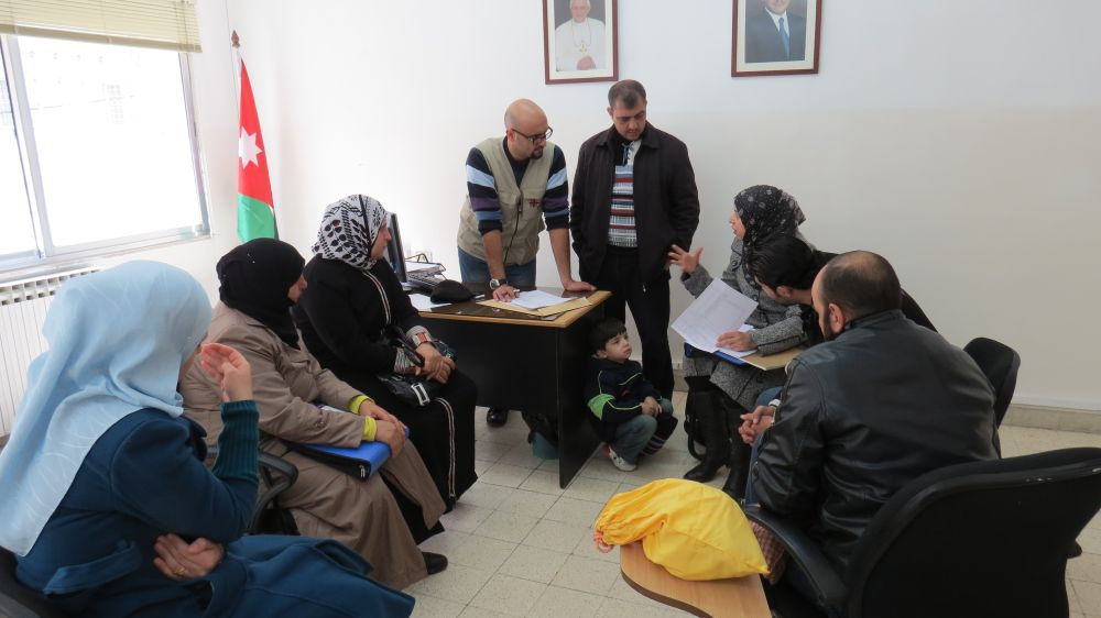 Tahani Injal (grey coat) talks with Caritas supervsor Laith Bsharat at a peacebuilding meeting in Zarqa.