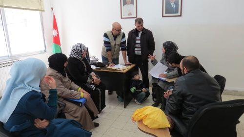 Tahani Injal (grey coat) talks with Caritas supervsor Laith Bsharat at a peacebuilding meeting in Zarqa.