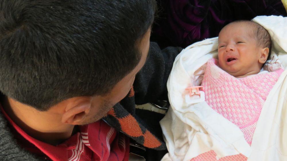 Fawaz and his daughter Maram wait at the caritas medical clinic in Amman.