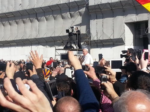 Pope Francis drives through as sea of flags, cameras and smart phones ahead of his inaugural mass. Credit: Caritas/Michelle Hough