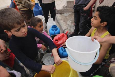 Children wait to collect water in Aleppo April 2, 2013. Around Syria, water shortages are worsening and supplies are sometimes contaminated, putting children at increased risk of diseases. REUTERS/Giath Taha