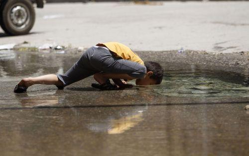 A boy drinks water from a burst water pipe in Aleppo. REUTERS/Muzaffar Salman