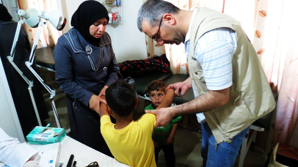 Dr. Joseph Homsi with Nour Al Hlwa and her children AbdelRahman and Yamen. Photo by Patrick Nicholson/Caritas