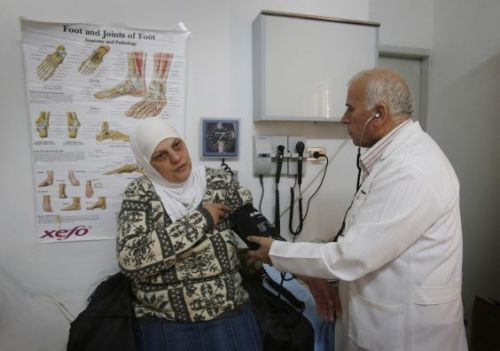 A Syrian refugee receives medical care from Doctor Joseph Shnoudi at a Caritas  Community Centre in Amman, Jordan. Credits: Danny Lawson/PA Wire